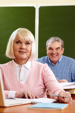 congenial: Portrait of blond female looking at camera with senior man  Stock Photo