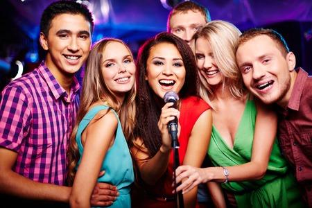 karaoke bar: Portrait of happy girls and guys singing in microphone in the karaoke bar  Stock Photo