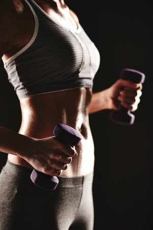 activewear: Body of slim female in activewear doing exercise with dumbbells