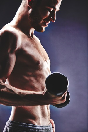 Image of handsome man with torso doing exercise with barbell photo