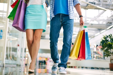 Legs of young couple going in the mall photo