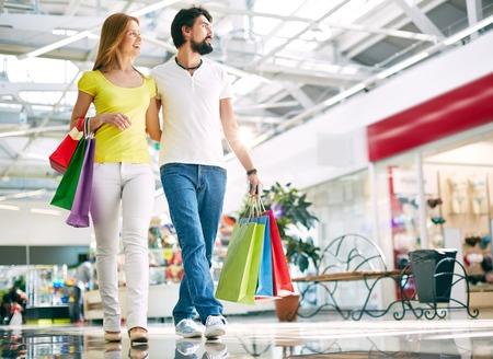 ショッピング モールを歩いて若いカップルの肖像画