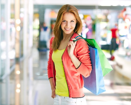 shopaholism: Portrait of happy girl with colorful shopping bags looking at camera