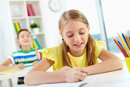 Lovely girl drawing at lesson on background of her classmate photo