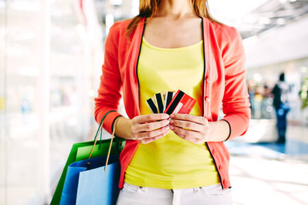 shopaholism: Female customer with plastic cards and shopping bags in the mall Stock Photo