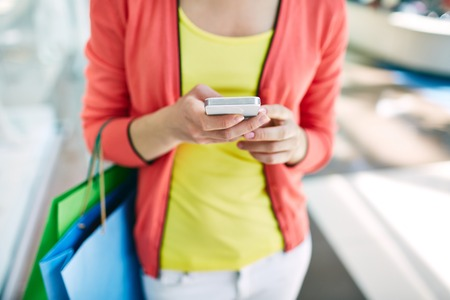 personal shopper: Female customer with cellular phone and shopping bags in the mall