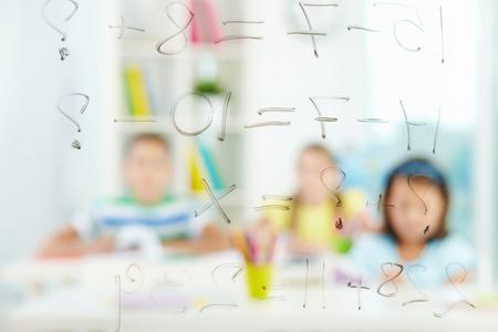 sumas: Imagen de las cantidades escritas a bordo transparente con compa�eros de escuela en el fondo Foto de archivo