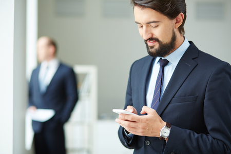 Image of young businessman using smartphone on background of his colleague photo