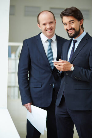 Image of young businessmen looking at camera in office photo