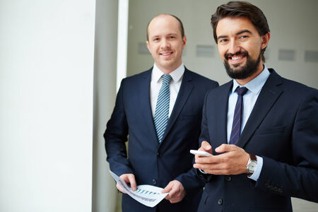 Image of two elegant businessmen looking at camera in office photo