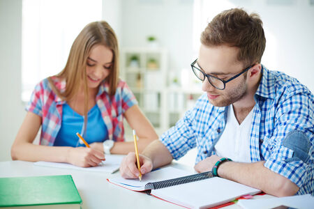 Successful student and his groupmate on background carrying out test at lesson Stock Photo