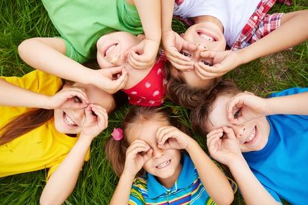 Группа милые дети, лежа на траве