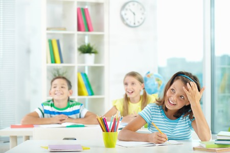 Portrait of cute girl and her two schoolmates on background looking at something attentively at lesson Stock Photo