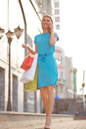 shopaholism: Portrait of happy girl with shopping bags calling outdoors