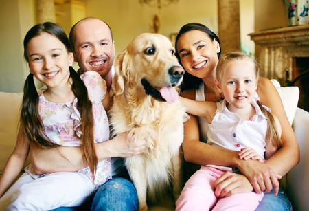 A young friendly family of four with pet looking at camera at home Banco de Imagens