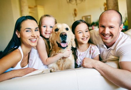 A young friendly family of four with pet looking at camera at home photo