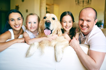 A young friendly family of four with pet looking at camera at home Stock Photo