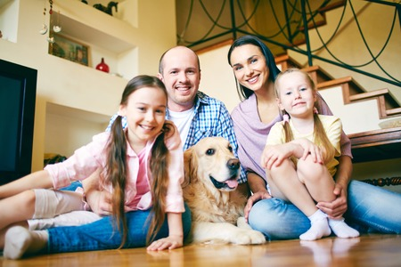 A young friendly family of four and their pet looking at camera at home