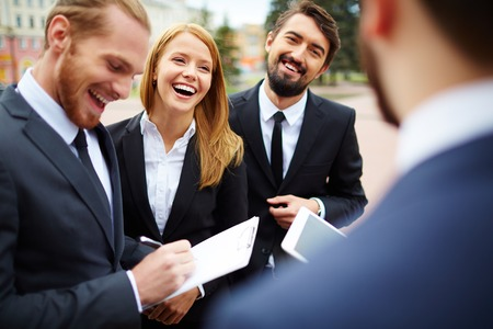 people: Happy businesswoman looking at colleague while discussing ideas at meeting outside Stock Photo