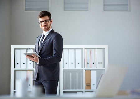 Handsome businessman looking at camera while networking in office