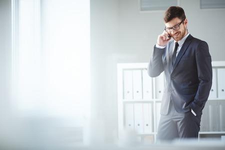 Knappe zakenman in pak en brillen spreken op de telefoon in het kantoor