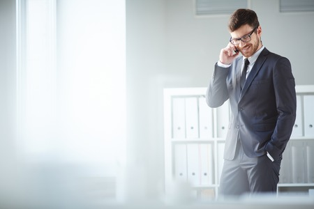 Pohledný podnikatel v obleku a brýle mluví na telefonu v kanceláři Reklamní fotografie