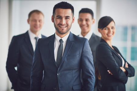 Portrait of confident business partners looking at camera with smiling leader in front photo