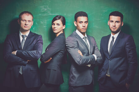 Group of elegant business partners looking at camera on green background photo