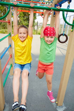 Happy little girls looking at camera on playground area photo