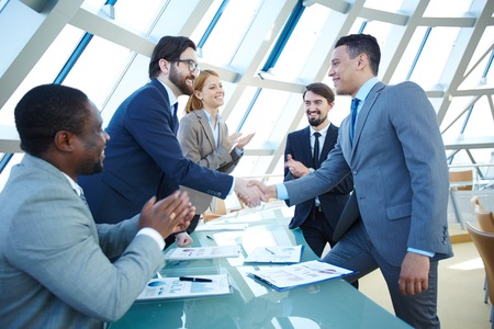 Group of business people congratulating their colleagues with striking grand deal Stockfoto