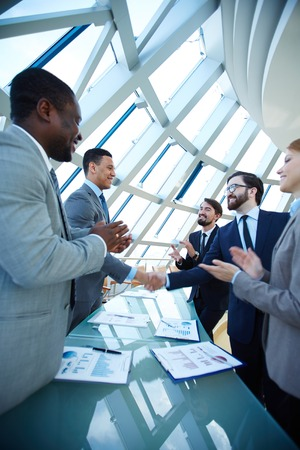 ovation: Group of business people congratulating their colleagues with striking grand deal Stock Photo
