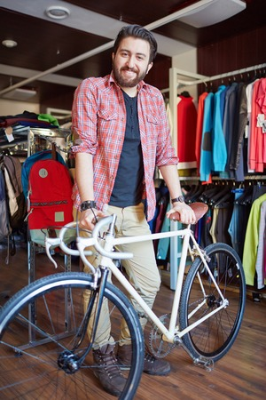 activewear: Portrait of a handsome man with bicycle looking at camera in sports shop Stock Photo