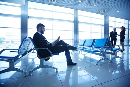 corporate travel: Businessman reading at the airport on background of colleagues talking by the window