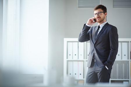 ハンサムなビジネスマンのスーツと眼鏡のオフィスで電話で話す