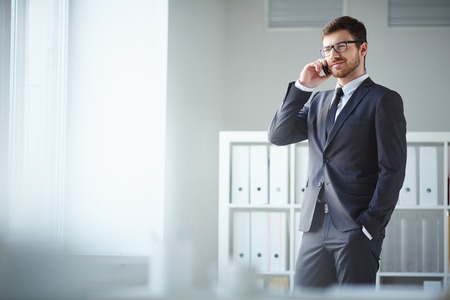 사무실에서 전화에 말하기 양복과 안경에 잘 생긴 사업가