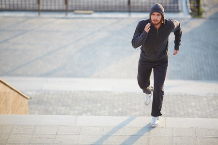 activewear: Portrait of young attractive sportsman running outside  Stock Photo