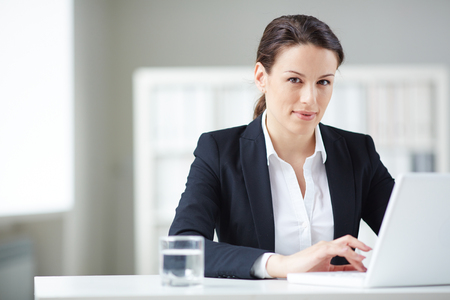 Young businesswoman typing and looking at camera in office photo