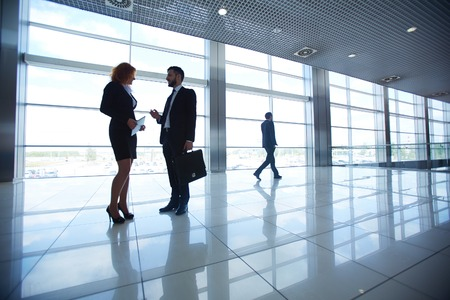 Two office workers discussing ideas on background of businessman photo