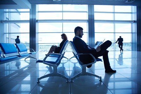 corporate travel: Two business partners reading at the airport on background of their colleagues by the window