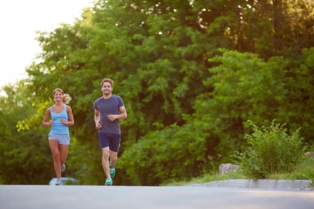 jogging in park: Photo of happy couple running outdoors Stock Photo
