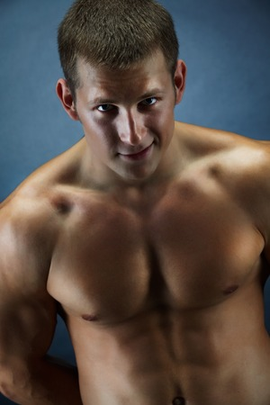 Image of handsome shirtless man looking at camera over dark background photo
