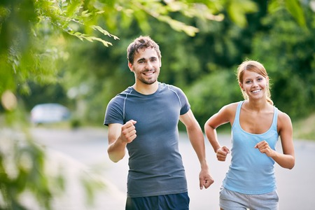 Photo of happy couple running in the morning outdoors photo