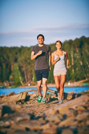 Photo of happy couple running outdoors Stock Photo