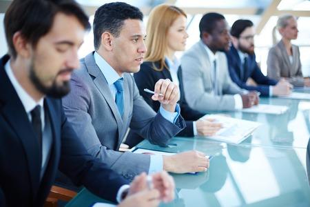 Joven hombre de negocios pensativa que escucha la explicación en el seminario rodeados de otros oyentes