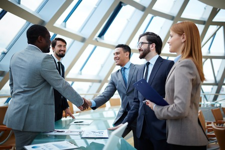 Two businessmen handshaking after striking grand deal photo