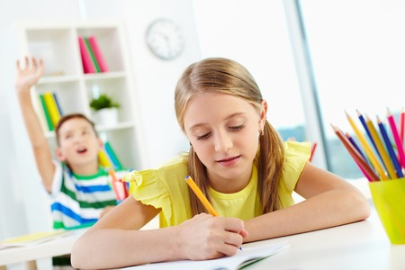schoolmate: Portrait of lovely girl drawing at workplace with schoolmate raising hand on background