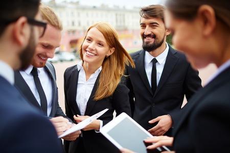 Groep van mensen uit het bedrijfsleven bespreken ideeën op vergadering buiten Stockfoto