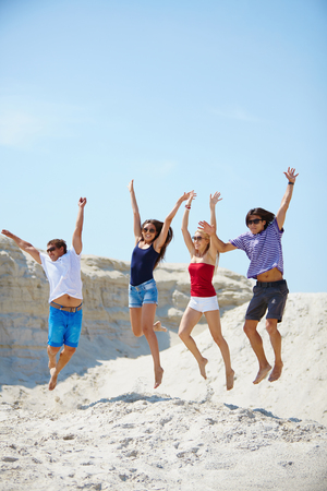 barefoot teens: Ecstatic young people holding by hands while jumping over sandy beach