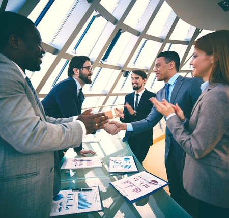 Group of business people congratulating their colleagues with promising deal photo