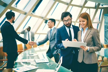 business project: Two business people discussing data or planning work on background of their colleagues handshaking Stock Photo